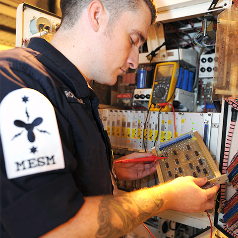 A Royal Navy engineer working on a submarine
